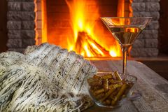 Glass of martini wine against cozy fireplace background, winter. Vacation, winter vacation, in country house, horizontal Stock Images