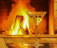 Martini in a glass before fireplace, in mansion, winter vacation,. Glass of martini wine; and wool; things against cozy fireplace background; winter vacation; in Stock Image