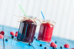Glass mason jar with raspberry and blueberry jam Royalty Free Stock Image