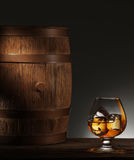 Glass of matured whiskey and old wooden barrel. Glass of matured whiskey with ice cubes in it and old wooden barrel Royalty Free Stock Image