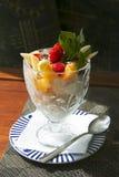 Glass med frukt och grated choklad i ett exponeringsglas Arkivfoto
