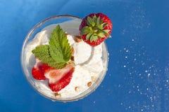 Glass med jordgubbar i ett exponeringsglas på en blå bakgrund royaltyfri bild