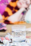 Glass with medicament and pile of pills on table Royalty Free Stock Image