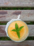 A glass of melon smoothie. Decorated by fresh peppermint leaves. A drink is placed on the wooden surface. Top view Stock Photo