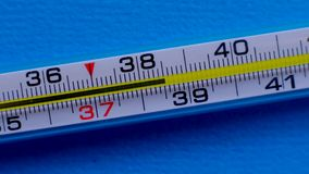 Temperature rising shown on a thermometer on a blue background close-up.
