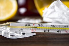 Glass mercury thermometer with a high temperature of 37.5 against the background of medicines, lemon, tea, folk remedies, tablets, Royalty Free Stock Photo