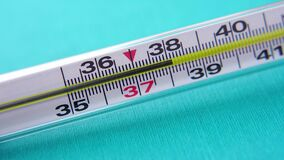 Glass mercury thermometer on a turquoise background. Increase in temperature to 39 degrees. Sign of pneumonia virus