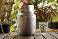 A Glass and Metal Jug of water Stock Photo