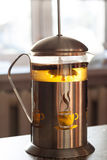 Glass-metal tea kettle. Brewed tea with lemon. Kitchen attributes for tea.  Royalty Free Stock Images