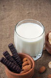 A glass of milk with almond nuts, corn flakes, chocolates,  on  burlap, sacks  background Stock Image
