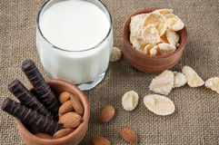 A glass of milk with almond nuts, corn flakes, chocolates,  on s Royalty Free Stock Photo