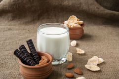 glass of milk with almond nuts, corn flakes, chocolates,  on sacking , burlap background Stock Photo