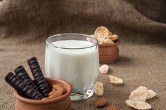 A glass of milk with almond nuts, corn flakes, chocolates,  on sacking burlap background Stock Images