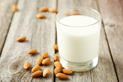 Glass of milk with almonds on the grey wooden background Royalty Free Stock Photo