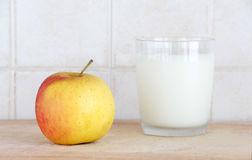 A glass of milk and an apple. A composition with a glass of fresh milk and an apple, on a wooden chopping board, inside a kitchen, landscape cut Royalty Free Stock Photos
