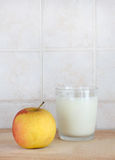 A glass of milk and an apple, space for text. A composition with a glass of milk and an apple, on a wooden chopping board, inside a kitchen, space for text on stock image
