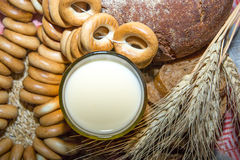 A glass of milk with bagels and bread. Stock Images