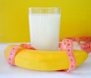 Glass of milk, a banana and a tape measure on a yellow background. Concept of diet Royalty Free Stock Photography
