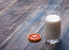 Glass of milk and biscuit. With red jelly on a wooden table Stock Photos