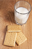 Glass of milk with biscuits. Glass of fresh milk with three biscuits on a wooden board Stock Photography