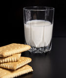 Glass of milk with biscuits. Glass of fresh milk with three biscuits on black background Royalty Free Stock Images