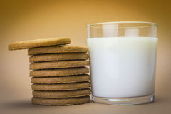 Glass of milk and biscuits round Stock Image
