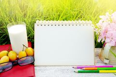 Glass of milk, blank page calendar, yellow fruit,sunglasses, pencils and pink flower on white wood table with green grass nature. Lifestyle background Stock Images