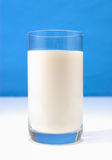 Glass of milk on blue Stock Photo