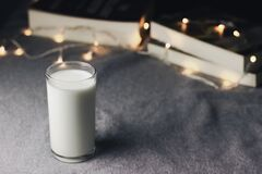 A glass of milk and books on table