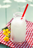 Glass milk bottle on checkered tablecloth Stock Image