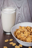 Glass of milk and bowl with cornflakes Royalty Free Stock Photo