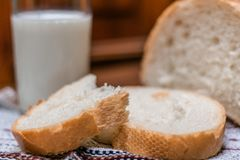 A glass of milk and bread on a wooden table. royalty free stock images