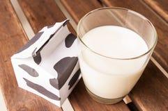 Glass of milk, a carton of milk. Glass of milk, a carton of milk on wooden table Stock Photo