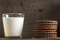 Glass of milk and chocolate biscuits on wooden table Stock Images