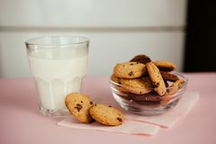 Glass of milk and chocolate chip cookies on the pink table. Simple breakfast Stock Image