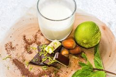 Glass of milk,chocolate pieces, hazelnut and lime fruit. Some delicacies - glass of milk, lime fruit, chocolate pieces, hazelnut, mint leaf and sprikled cocoa Royalty Free Stock Images
