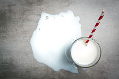 Glass of milk on a concrete table. Glass of milk and a red and white drinking straw on a concrete table. It is a puddle of milk on the table. Crying over spilt Royalty Free Stock Images