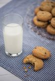 A glass of milk and a cookie with a bite taken out of it sit on. A blue gingham napkin with a plate of cookies in the background Royalty Free Stock Images