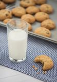 A glass of milk and a cookie with a bite taken out of it sit on stock images