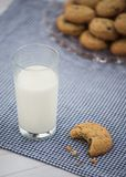 A glass of milk and a cookie with a bite taken out of it sit on. A blue gingham napkin with a plate of cookies in the background Stock Photography