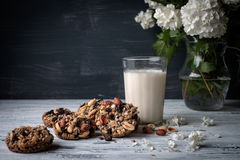 Glass of milk and cookies made of nuts and raisins Stock Photos