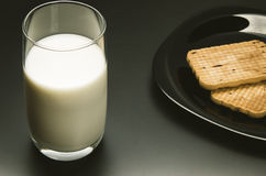 Glass with milk and cookies in a plate on a black background. Glass with milk and a plate with cookies on a black background Royalty Free Stock Image