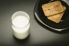 Glass with milk and cookies in a plate. The top view Royalty Free Stock Image