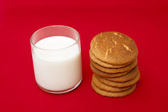 Glass of milk and cookies. On a red background Stock Image
