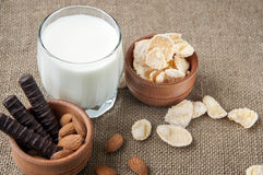 A glass of milk with cookies on a wooden board on a background sacking, burlap Royalty Free Stock Photography