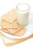Glass of milk and crackers over table-napk. Glass of milk and dish of crackers over table-napkin isolated on white background royalty free stock photography