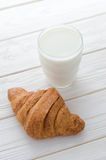 Glass of milk and a croissant on the table. Royalty Free Stock Photography