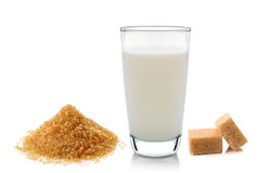 Glass of milk and cubes of cane sugar Stock Photos