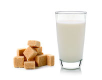 Glass of milk and cubes of cane sugar Stock Images