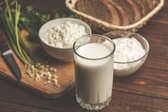 Glass of milk, curd in bowl, cheese cream, fresh bred and green herb on wooden cutting board as ingredients. For homemade healthy diet vegetarian food Royalty Free Stock Image
